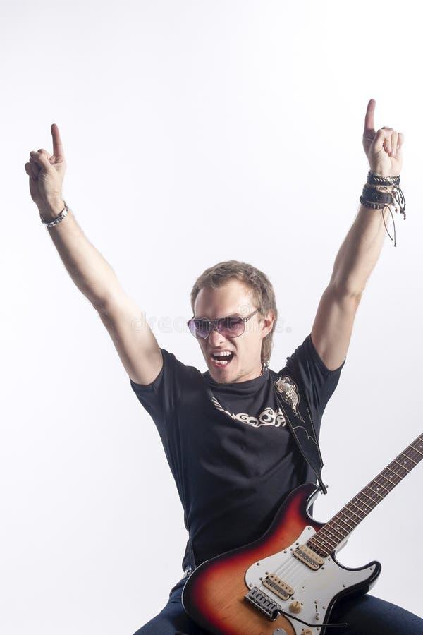 音乐样式和想法 摆在与仪器的年轻传神白种人男性吉他弹奏者反对白色 图库摄影