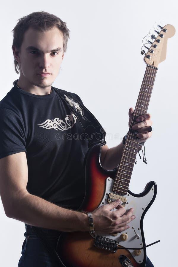 音乐概念和想法 摆在与仪器的白种人男性吉他演奏员画象反对白色 库存照片
