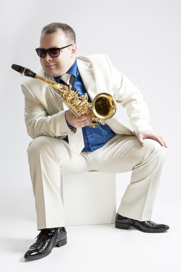 音乐概念和想法 Hadnsome男性萨克管演奏员画象摆在白色衣服的太阳镜的 图库摄影
