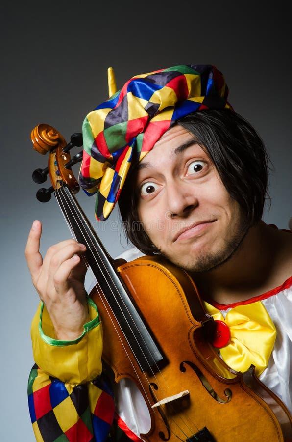 音乐概念的滑稽的小提琴小丑球员 免版税库存照片