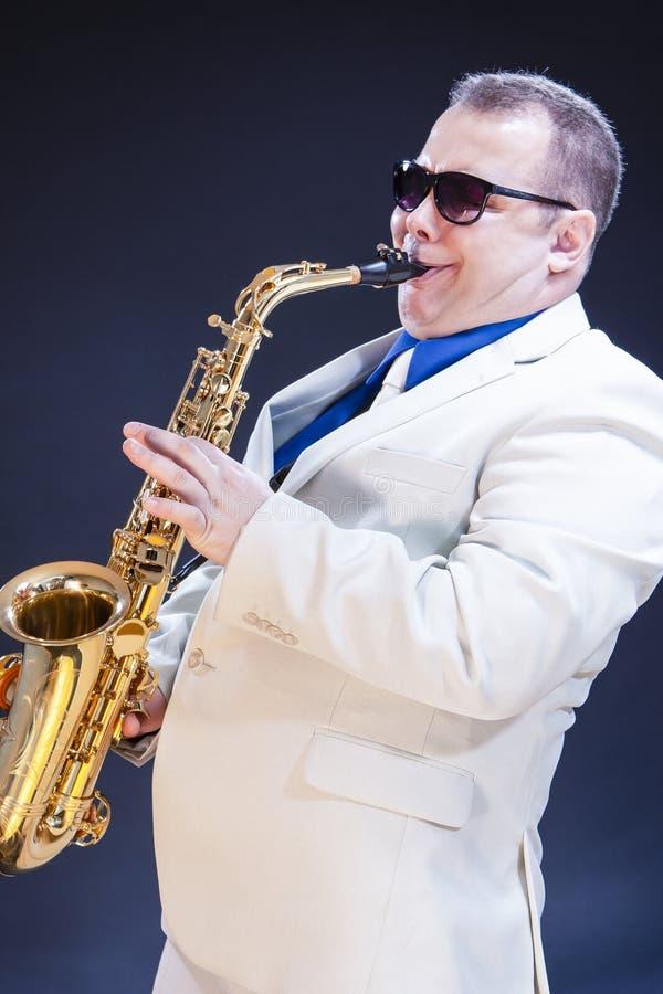 音乐概念 传神成熟使用的萨克斯管吹奏者 库存图片