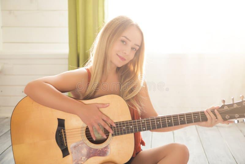 音乐概念 女孩吉他使用 音乐松弛妇女 在家弹吉他的美丽的女孩 库存照片
