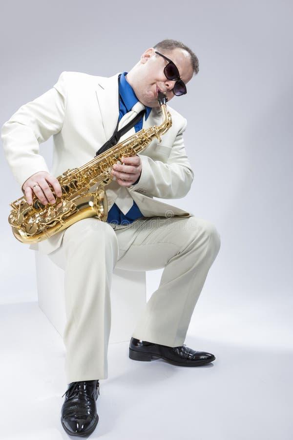 音乐概念 弹女低音萨克斯管的白种人成熟男性音乐家 免版税库存照片