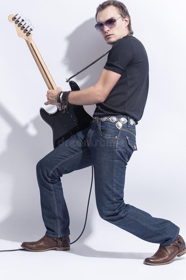 音乐概念 摆在与吉他的英俊的男性吉他弹奏者反对白色 免版税库存照片