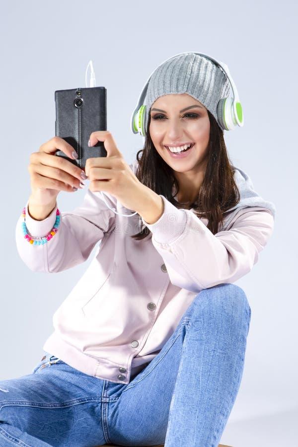 音乐概念 桃红色有冠乌鸦的正面愉快的白种人深色的女孩 库存照片