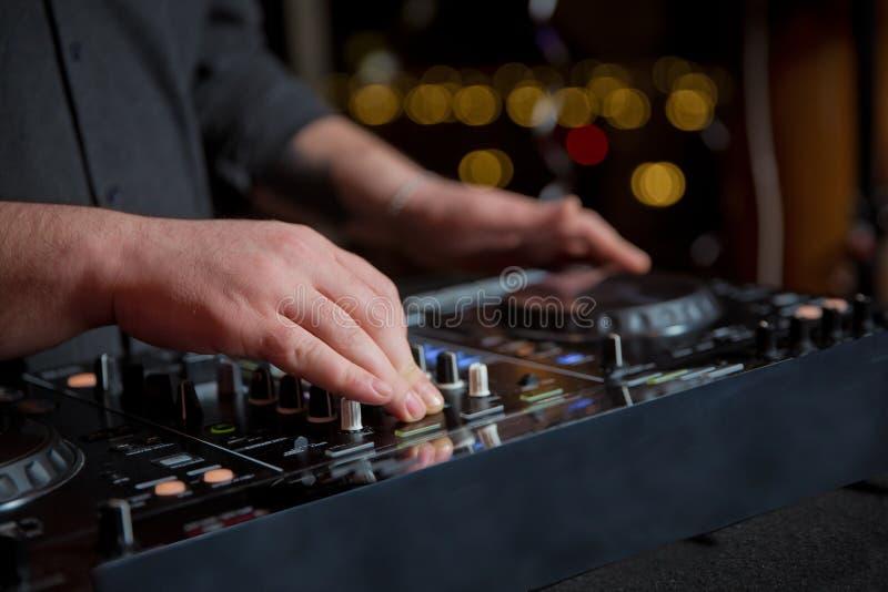 音乐概念 DJ是与控制器和搅拌器的节奏音乐 DJ播放歌曲在党 年轻人调整音乐 库存图片