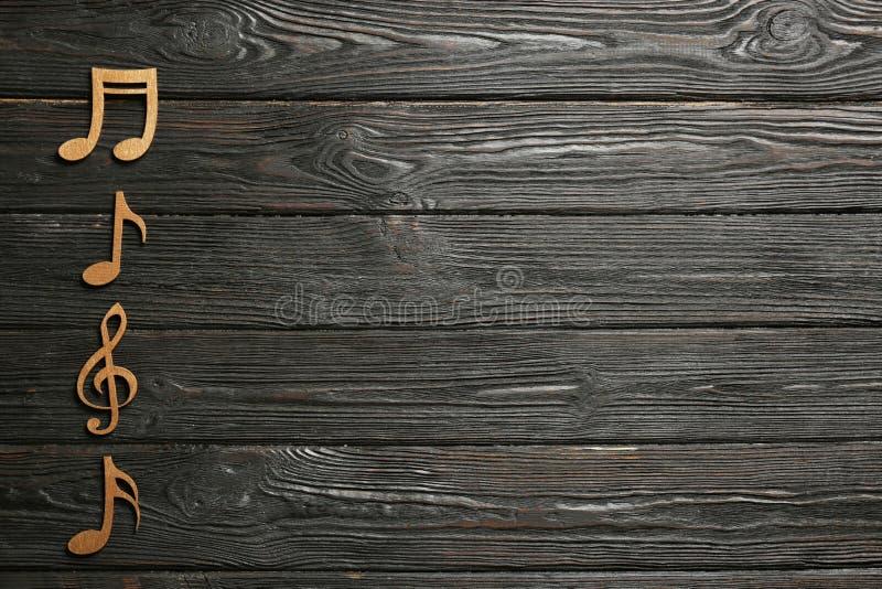 音乐笔记和高音谱号在木背景,顶视图 图库摄影