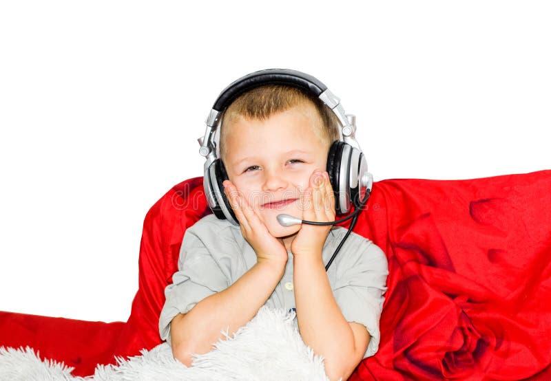 音乐耳机的男孩有话筒的用面孔的人工拧紧 免版税库存照片