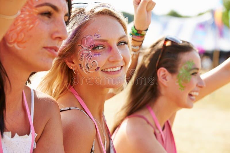 音乐节的,一三个女朋友转向了照相机 库存照片