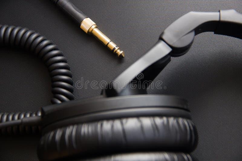 音乐设备、专业演播室黑色耳机和起重器绳子 从上面关闭  库存照片