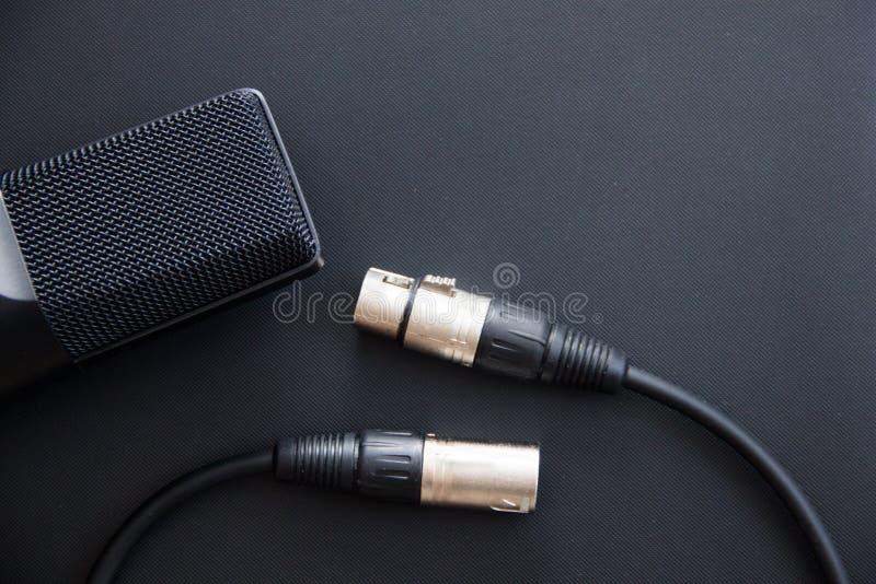 音乐设备,有xlr缆绳的,暗色专业冷凝器演播室话筒 从上面关闭  免版税库存照片