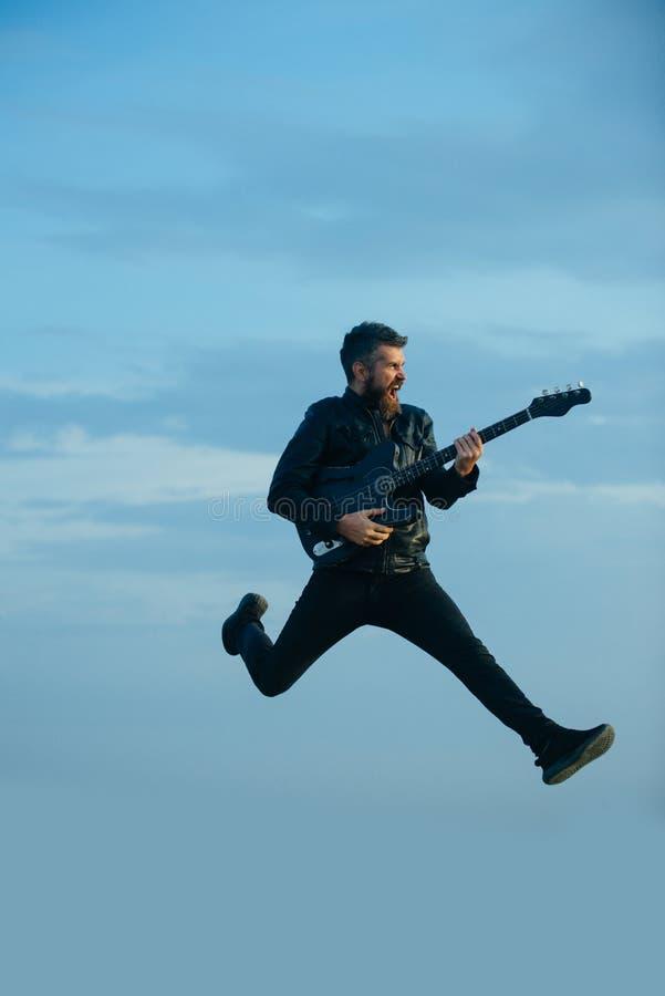 音乐非常是乐趣 有胡子的人跳与在蓝天的吉他 有胡子的行家吉他弹奏者在激动的面孔戏剧 库存照片