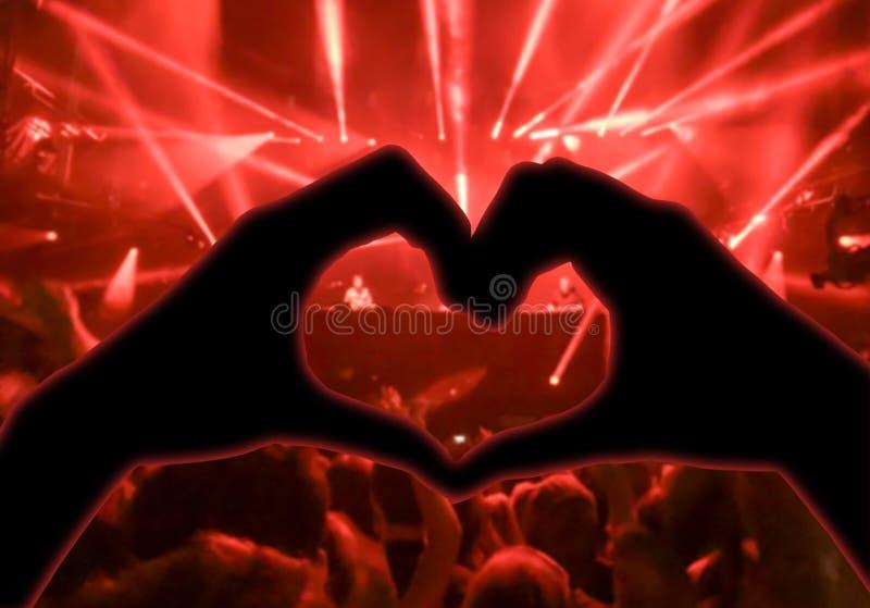 音乐音乐会,手被举以音乐的心脏的形式,弄脏了人群和艺术家阶段的在背景中 库存图片