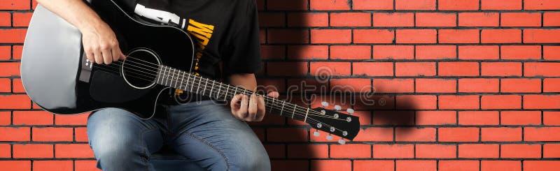 音乐-片段人戏剧一把黑声学吉他 库存照片