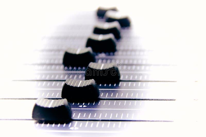 音频搅拌器、混合的书桌控制和音量控制器、音乐混合的控制台有被贬低的作用的横幅的和背景 库存照片