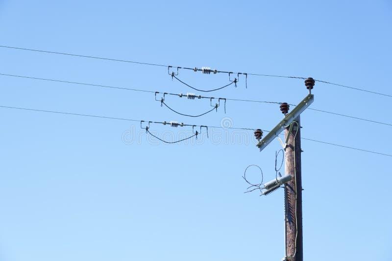 顶上的电线电话电缆导线危险电杀害蓝天背景电力输送distribut 免版税库存图片
