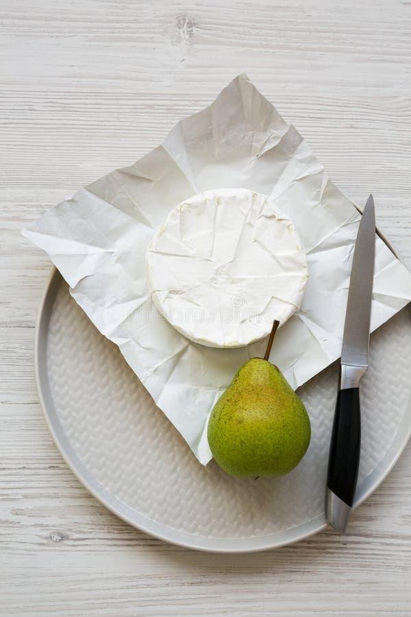 头顶的景色,纸上的卡芒贝尔奶酪,盘子上的新鲜梨 酒类食品 平铺,顶视图,从上方 免版税库存照片