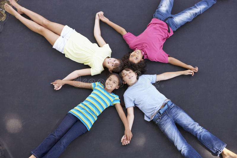 顶上的观点的一起说谎在绷床的小组孩子 免版税库存图片