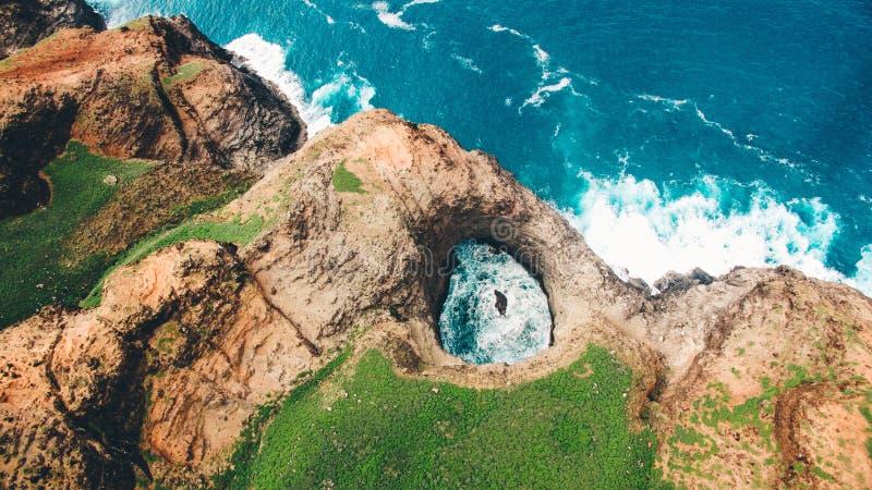 顶上的ariel射击了在Kaua'i Na帕利海岸的美丽的OpenCeiling海洞与绿叶的 库存图片