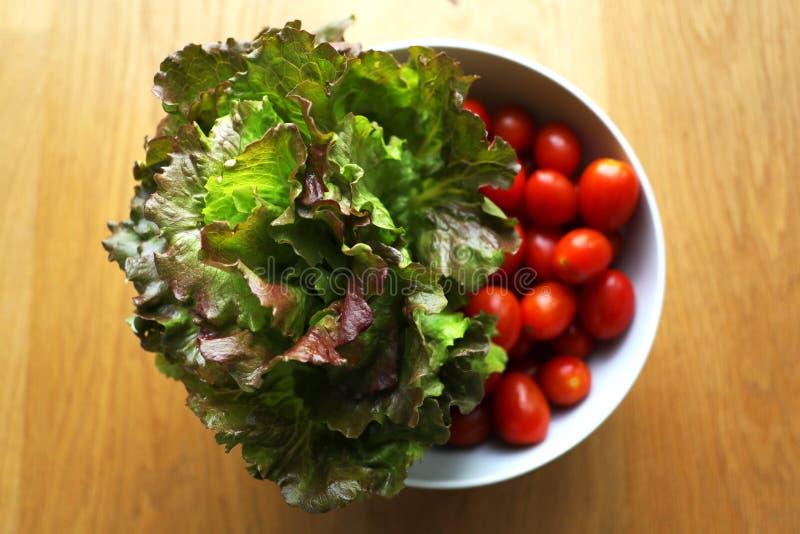 顶头束莴苣用在一个白色陶瓷碗的樱桃李子红色发光的蕃茄在木背景 库存图片