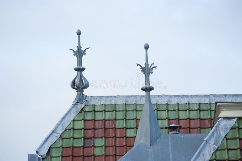 顶房顶上面与装饰品和绿色棕色瓦片 库存图片