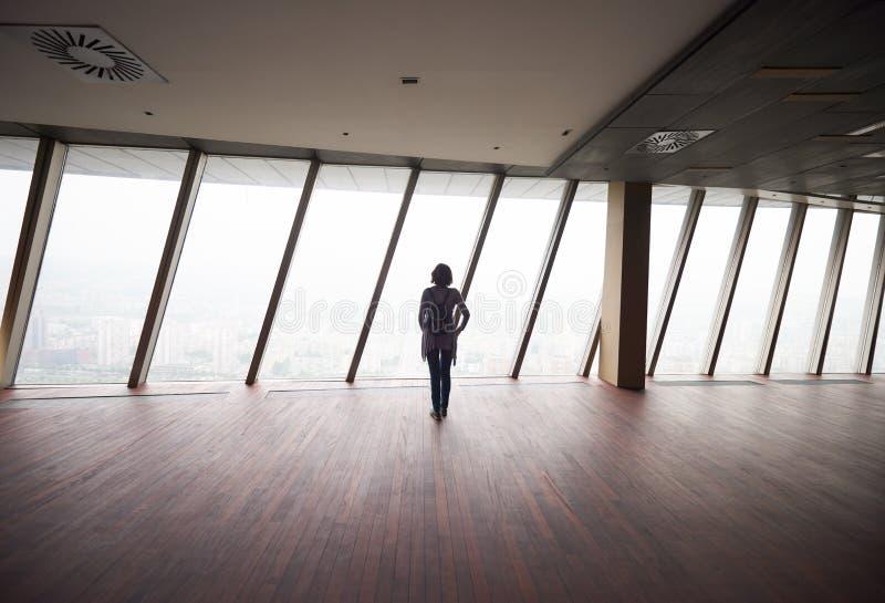 顶楼房屋公寓的年轻成功的妇女 免版税库存图片