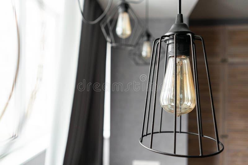 顶楼样式有一个电灯泡的铁灯罩在现代公寓的内部客厅 葡萄酒样式电灯泡 免版税库存图片
