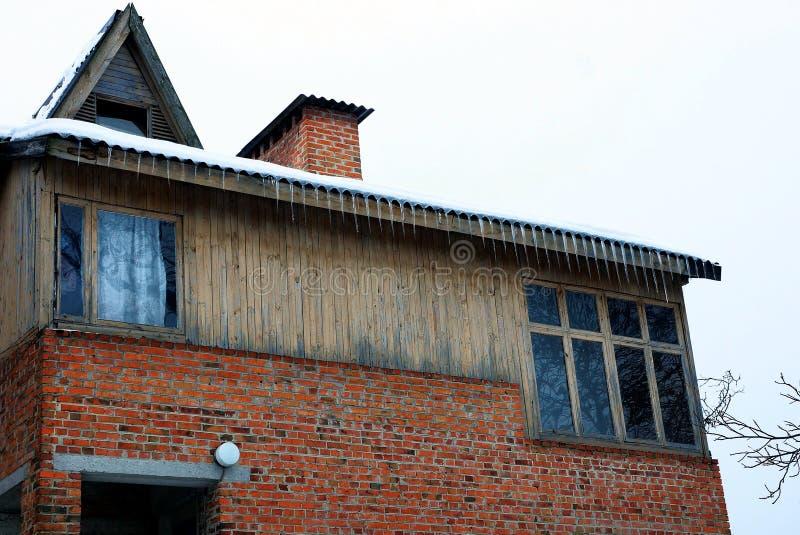 顶楼砖和木板条褐色房子与窗口和冰柱在屋顶 库存照片