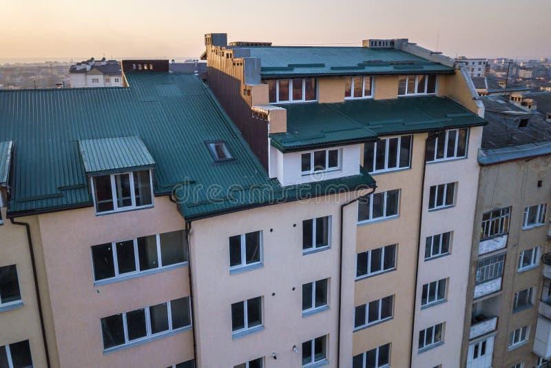 顶楼附录与塑料窗口、用绿色金属支持的板条盖的屋顶和墙壁的室外部鸟瞰图,新的天沟 免版税库存照片