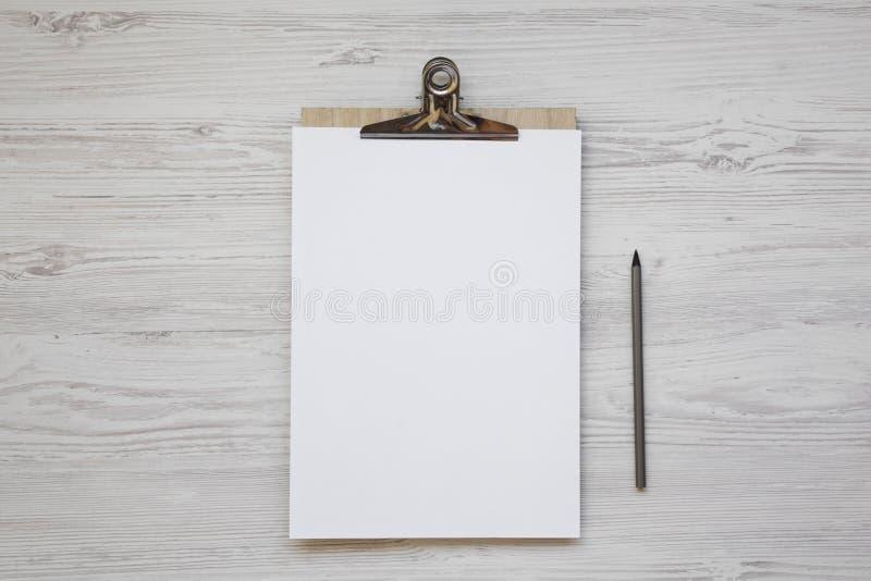 顶视图、剪贴板有空白的纸片的和铅笔在白色木背景 平的位置,顶上 库存照片