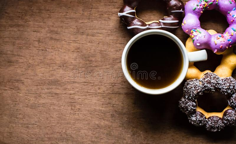 顶视图、多福饼、巧克力、甜点和热的咖啡或者阿梅里卡诺 在木桌上 库存图片