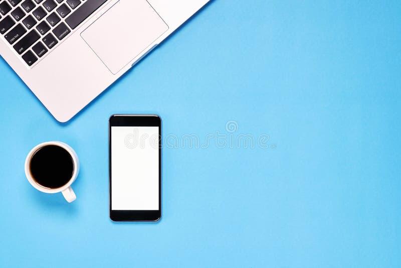 顶视图、现代工作场所有膝上型计算机的和智能手机,咖啡 安置在淡色背景 免版税库存照片