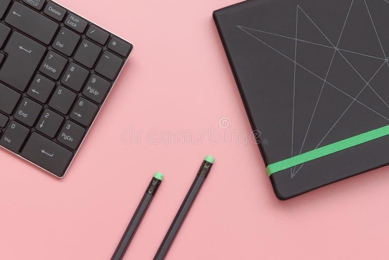 顶视图、笔记本和铅笔有键盘的在桃红色背景 特写镜头 免版税图库摄影