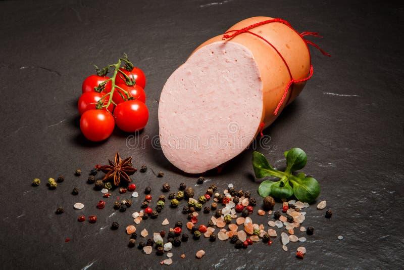 顶视图一半切的煮沸的香肠供食用香料和蓬蒿 库存照片