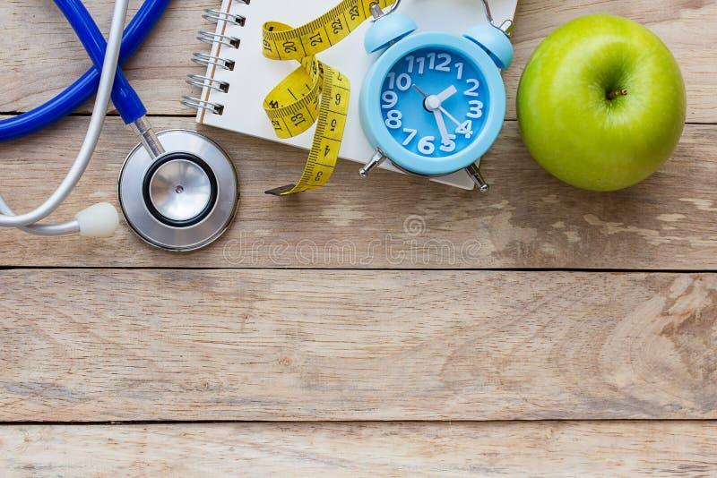 顶视图与蓝色听诊器和笔记本的绿色苹果在木头 免版税库存图片
