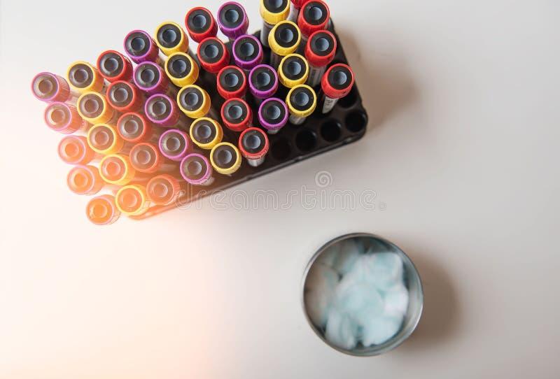 顶视图五颜六色的样品血液管和注射器,从患者的棉花在实验室 免版税库存照片