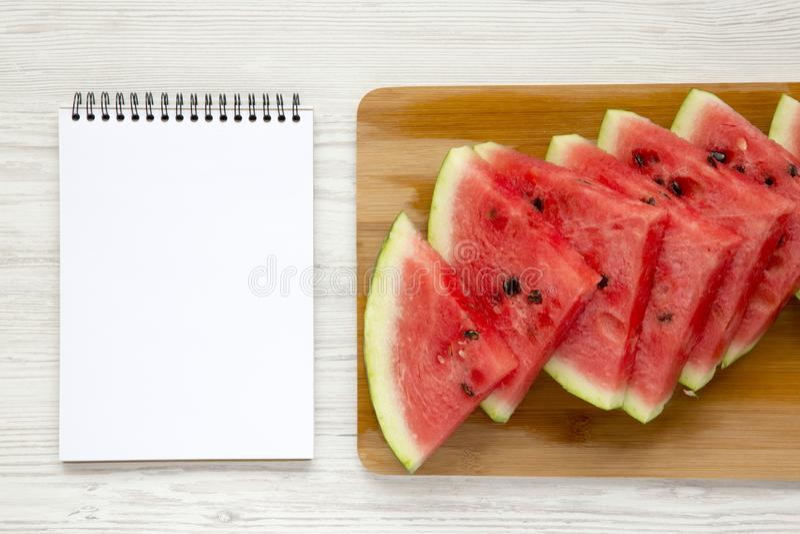 顶视图切了在切口竹委员会的新鲜的水多的西瓜有在白色木背景的空白的笔记本的 库存照片