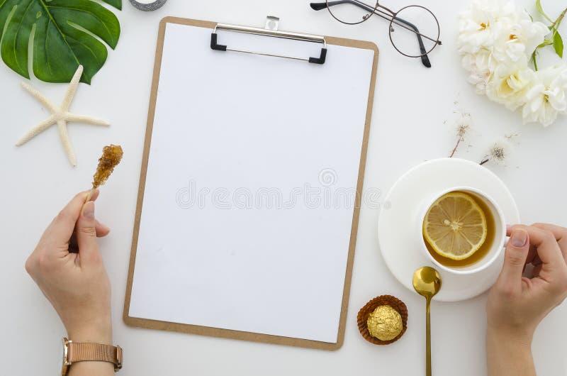 顶视图办公桌笔记板大模型 女孩拿着茶用柠檬,工作区用白玫瑰装饰 库存图片