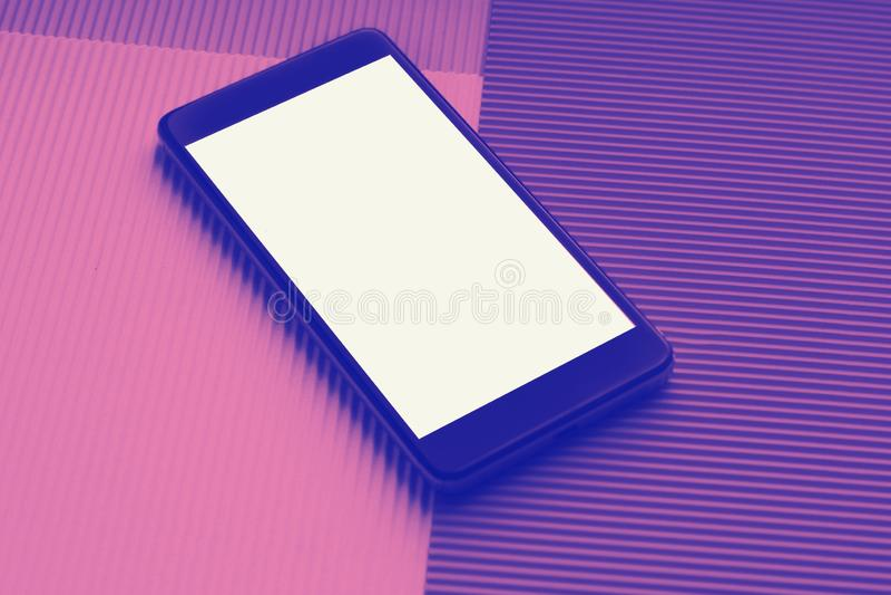 顶视图反对时髦多色背景的大模型智能手机 免版税库存照片