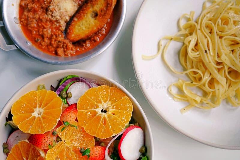 顶视图和关闭饭桌、沙拉和意大利细面条在白色盘和一张白色桌安置的博洛涅塞 免版税图库摄影