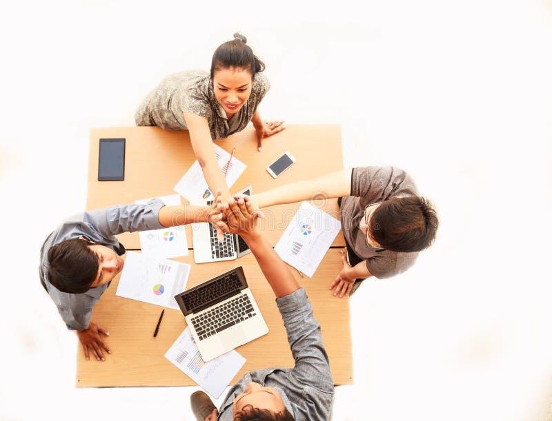顶视图商人和女实业家身分和高五在会议,拷贝空间移交桌在被隔绝的白色背景 免版税库存照片