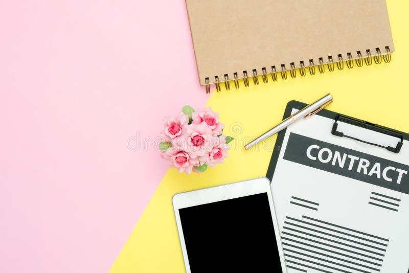 顶视图嘲笑合同、笔和黑屏幕片剂,有玫瑰的笔记本在与拷贝空间的桃红色黄色淡色 免版税图库摄影