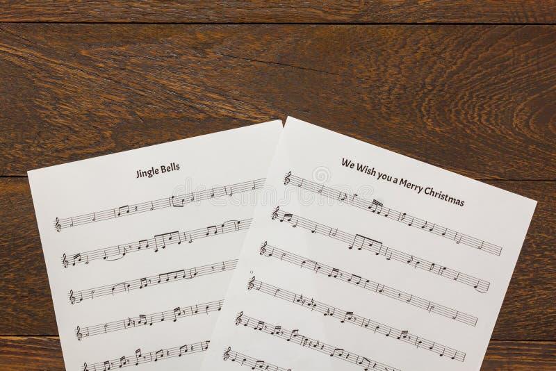 顶视图圣诞节音乐在木桌背景的便条纸 C 免版税库存图片