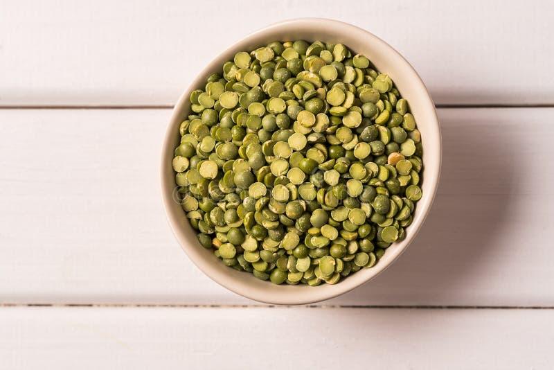 顶视图在一个碗的绿色扁豆在白色木背景 免版税库存照片