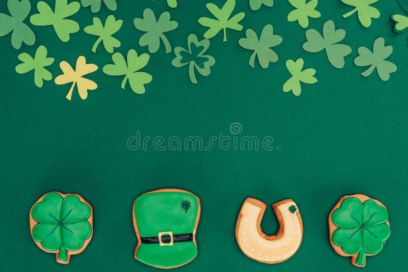 顶视图在绿色和纸三叶草隔绝的结冰曲奇饼, st patricks天概念 免版税库存图片