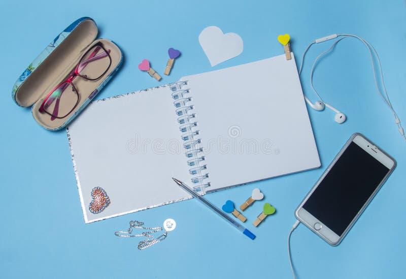 顶视图在蓝色背景的工作区大模型与笔记本、笔、咖啡、夹子和辅助部件 库存照片