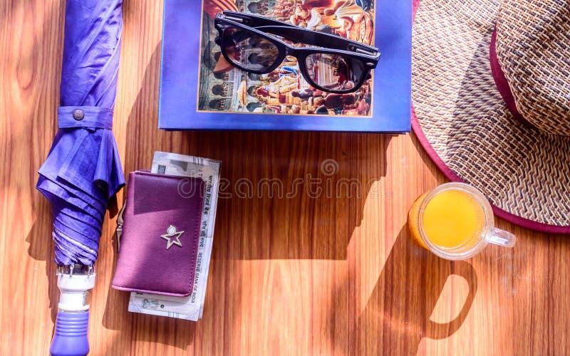 顶视图夏天妇女海滩背景旅行辅助部件 太阳镜、金钱钱包、书、伞、草帽和玻璃  免版税图库摄影