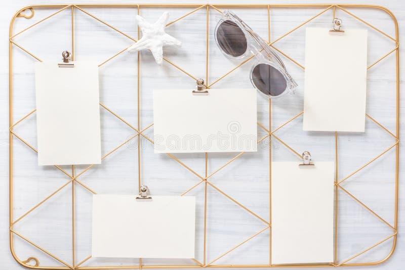 顶视图套笔记本夹子框架和星鱼石头与太阳镜在白色木桌上 o 免版税库存图片