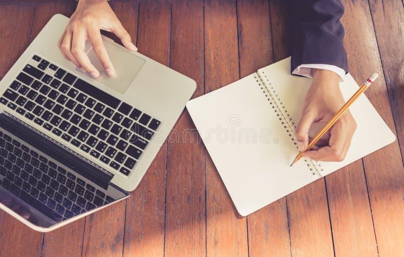 顶视图女商人在笔记本在咖啡店葡萄酒口气写并且使用膝上型计算机工作室外 免版税库存图片