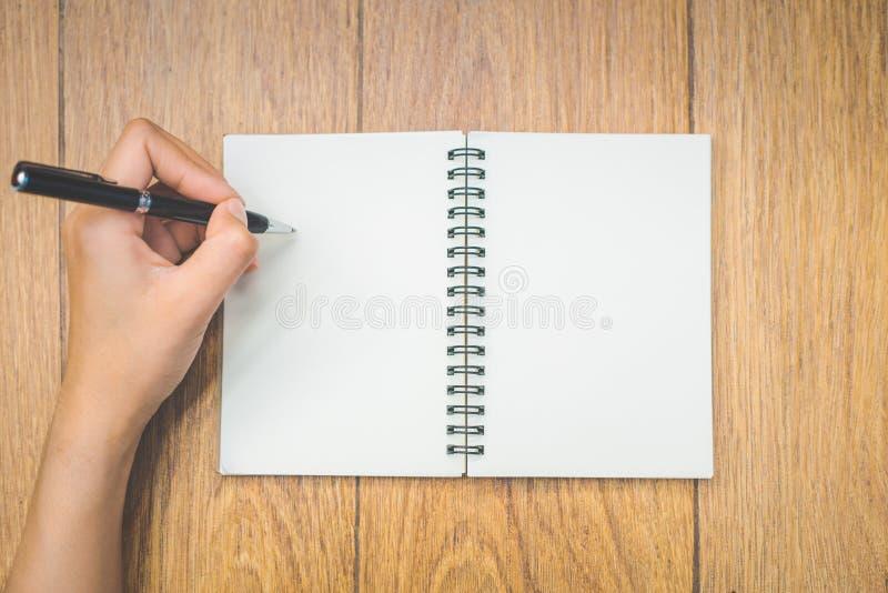 顶视图妇女手在与笔的一个空白的笔记薄书写  免版税库存图片